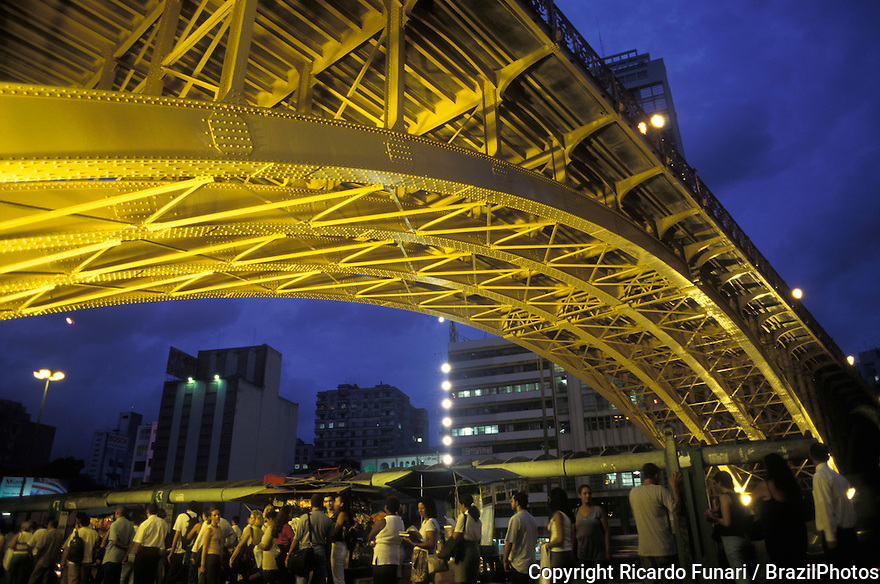 Bus stop below Santa Efigenia Viaduct, a yellow metallic construction in downtown Sao Paulo, Brazil - people in line waiting for the bus.
