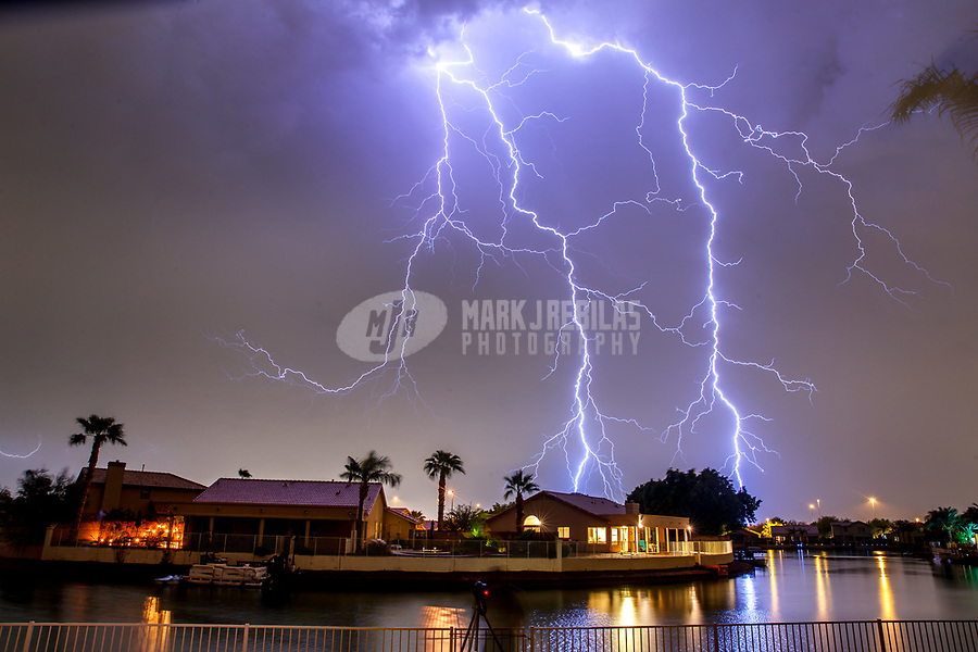 Aug 23, 2017; Glendale, Arizona, USA;   Lightning strikes near houses on the water in the Arrowhead Lakes residential community during a summer monsoon thunderstorm. Mandatory Credit: Mark J. Rebilas
