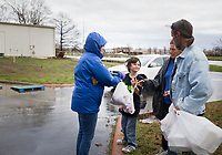 """Rachel Petree, human resources and accounting manager, (from left) distributes food toDevin Birkes, 12, Tia Birkes and James Birkes of Rogers, Thursday, March 19, 2020 at the Samaritan Community Center in Rogers. Check out nwaonline.com/200320Daily/ for today's photo gallery. <br /> (NWA Democrat-Gazette/Charlie Kaijo)<br /> <br /> In response to the covid-19 crisis, Samaritan decided to convert all of their feeding operations to drive through operations. They started on Monday in Springdale and expanded to Rogers on Tuesday. They are running their Cafe by providing hot meals, running their market by providing groceries and running their snack pack program by providing snack packs along with the groceries people pick up. Compared to a normal week, they've doubled their numbers in Rogers and tripled their numbers in Springdale. Running Monday through Thursday. """"We're trying to do the same thing we always do. We're just serving more people,"""" said Debbie Rambo, executive director. Since revenue is down from their thrift stores, their main funding sources, they are asking people to donate by visiting samcc.org. People can also donate over the phone or they can mail a check to P.O. Box 939 in Rogers, 72757"""