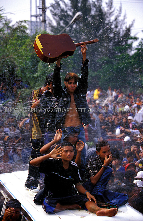 4/13/2002--Rangoon, Burma..At the Lay Phyu and Iron Cross concert a fan holds up a guitar as he passes the stage. During the New Year's concerts, water is sprayed on concer goers as a traditional blessing. Cars weave through the crowds carrying rock fans from stage to stage scattered around Rangoon...The annual outdoor free concerts are held every April duirng Burma's traditional New Year celebrations. Normally gatherings of young men woiuld be broken up by Burma's ruling junta but the concerts are the one time of year such large gatherings are allowed. Local authorities are nervous that such concerts may turn political or violent and watch the shows carefull for signs of unrest...All photographs ©2003 Stuart Isett.All rights reserved.