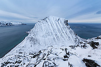 Nonhammarenveggen mountain peak rises from the sea in winter, Vestvågøy, Lofoten Islands, Norway