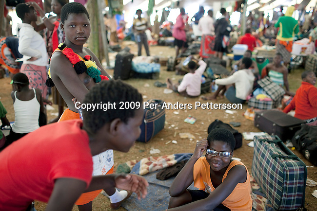 LUDZIDZINI, SWAZILAND - AUGUST 30: Unidentified girls dress and prepare before a traditional Reed dance ceremony at the Royal Palace on August 30, 2009, in Ludzidzini, Swaziland. About 80.000 virgins from all over the country attended this yearly event, which goes on for a week and which is the biggest in Swazi culture. Many of the girls stayed in tents and slept on the ground. It was founded to celebrate the beauty of Swazi women and girls. King Mswati III, and absolute monarch, was born in 1968 and he has 14 wives and many children. The king danced with his men in front of the 80.000 girls. Many of the girls hope to get noticed by the king and to be chosen as a future wife, a ticket from poverty and into a life of privilege and luxury. The country is one of the poorest in the world and it is struggling with a high prevalence of HIV-Aids and severe poverty. (Photo by: Per-Anders Pettersson)...