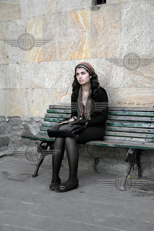 A young woman sits on a bench in Tbilisi.
