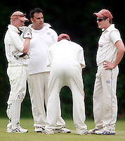 Highgate players discuss tactics during the Middlesex County Cricket League Division Three game between Highgate and Hornsey at Park Road, Crouch End, London on Sat June 5, 2010