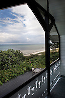 A balcony under the eaves has views of the beach and the coastline