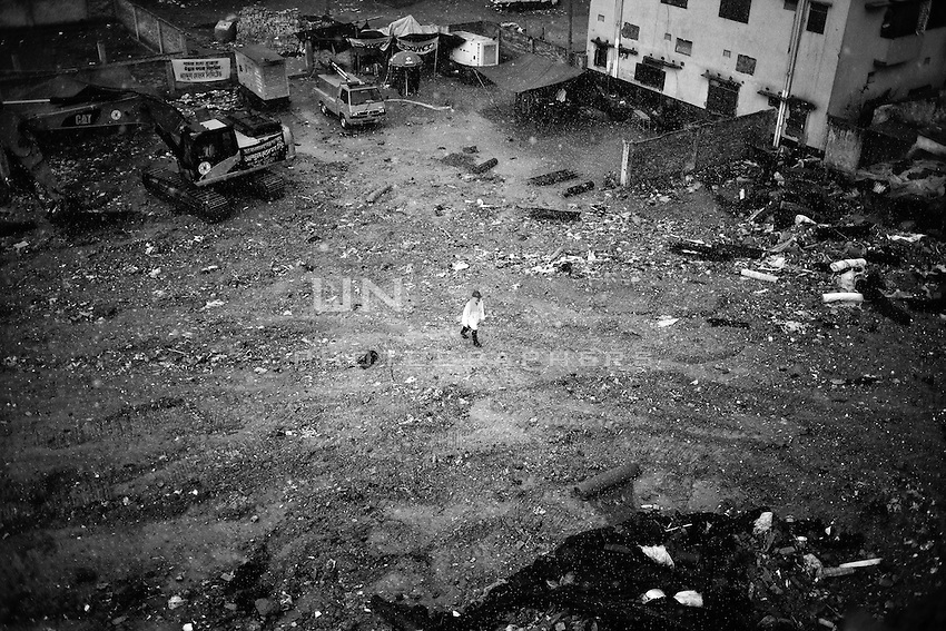 A rescue worker walking in the rain towards collapsed building Rana plaza in Savar, near Dhaka, Bangladesh.