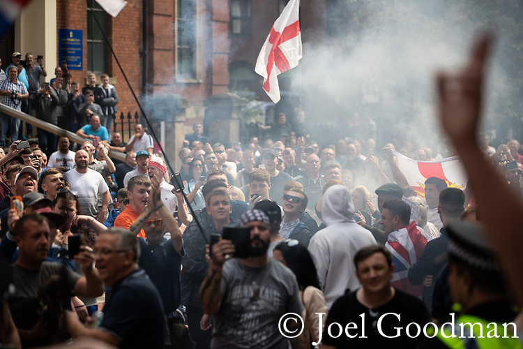 © Joel Goodman - 07973 332324 . 01/06/2018 . Leeds, UK. A smoke bomb is set off outside Leeds Crown Court . Supporters of EDL founder Tommy Robinson ( real name Stephen Yaxley-Lennon ) demonstrate in Leeds after Robinson was convicted of Contempt of Court . Robinson was already serving a suspended sentence for Contempt of Court over a similar incident , when he was convicted on Friday 25th May 2018 . Reporting restrictions , since lifted , initially prevented coverage of Robinson's arrest and incarceration . Photo credit : Joel Goodman