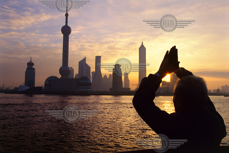 Old man performing morning exercises on the Bund, facing towards the rising sun and the new skyscrapers of Pudong District, including the 457m Oriental Pearl TV Tower.