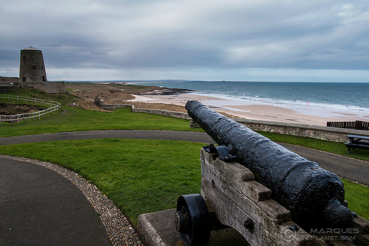 An old canon aimed at the coast beyond the walls of Bamburgh Castle, England.  .The Bamburgh Castle is one of the largest inhabited castles in the UK. Located in northeast England, right by the beach on the shores of Northumberland. With a recorded history going back to the year 547, Bamburgh Castle played a central role in many of the historic periods of this region..In 1894, Bamburgh Castle was bought by Lord William Armstrong for £60,000. To this day the castle is inhabited by the Armstrong family.