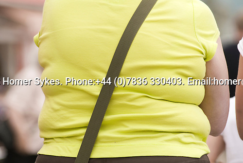 Ordinary fat woman on holiday Wales. Rear view wear yellowish T shirt and brown shoulder bag strap across back. Three rolls of fat.  UK 2008.