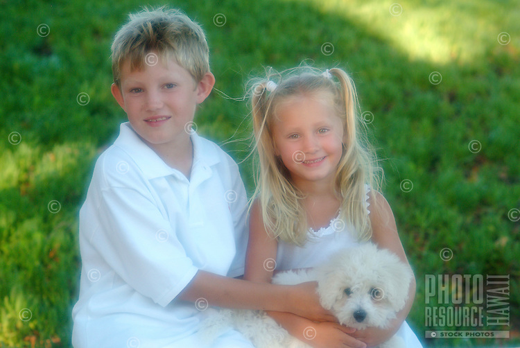 Brother and sister holding bichon frise puppy