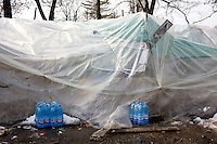 ROMANIA / Bucharest / 21.02.09..Bottles of spring water outside makeshift plastic tents across rom the Chinsese Embassy...Hundreds of Chinese immigrants are currently stuck in Romania after their work contracts with construction firms here were suddenly terminated in late January. They expected to make at least 800 Euros per month, or double what they can make in China as agricultural laborers. About 80 of them are camped out under plastic sheeting in front of the Chinese Embassy hoping to get some kind of help. During the day, hundreds more are joining them to stage a protest. They paid a Chinese broker 10,000 Euros a piece for the lucrative four year construction contracts and are hoping to get reimbursed in order to be able to buy tickets home. The immigrants are relying upon the help of generous Romanians who pull up and deliver food from their cars. The economic crisis hit Romania just as many of the immigrants arrived in November. ...© Davin Ellicson / Anzenberger