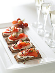 Elegant squares of toast with soft cheese and smoked salmon lox, with glasses of champagne