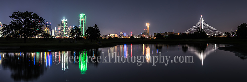 Dallas skyline reflections pano in downtown.  This image of the Dallas Cityscape includes the Margaret Hunt Hill Bridge, the Reunion Tower, Bank of America, Renaissance Tower, and many more of the city's high rises buildings This skyline reflects back into the waters of the Trinity river with the buildings and bridge along with those iconic skycrapers reflections in the water of the Trinity.