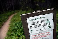 A sign warns hikers that they are entering so-called Grizzly Country on the trail to Grinnell Glacier in the Many Glacier section of Glacier National Park, Montana, USA.