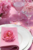 Confetti mingled with rose petals is scattered on the pink cloth of a rose-themed wedding table