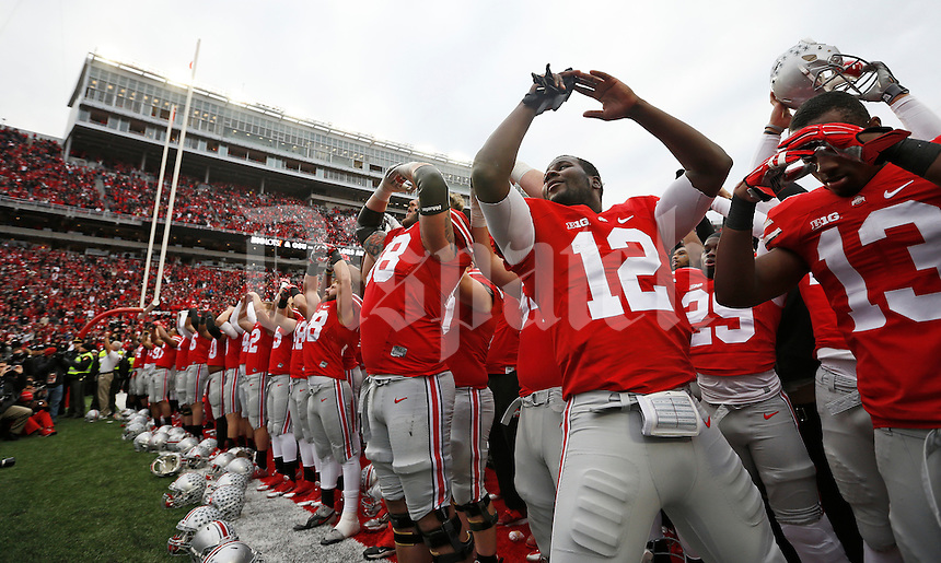 Ohio State Buckeyes quarterback Cardale Jones (12) sings Carmen Ohio with teammates following the NCAA football game against the Michigan Wolverines at Ohio Stadium on Nov. 29, 2014. The Buckeyes won 42-28. (Adam Cairns / The Columbus Dispatch)