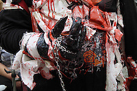 Close up of part of dress of a zombie walk participant. Hand with with blood on and a chain around the wrist.
