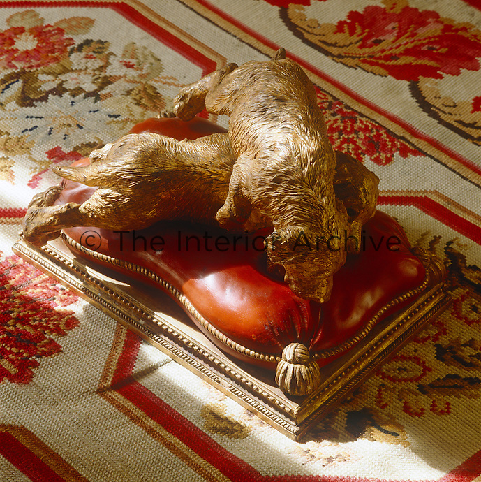On the Aubusson carpet in the library is one of a pair of carvings depicting dogs playing on a scarlet cushion