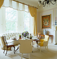 The lacquered lavender dining room has a pair of pedestal tables, one paired with a curved sofa in the bay window