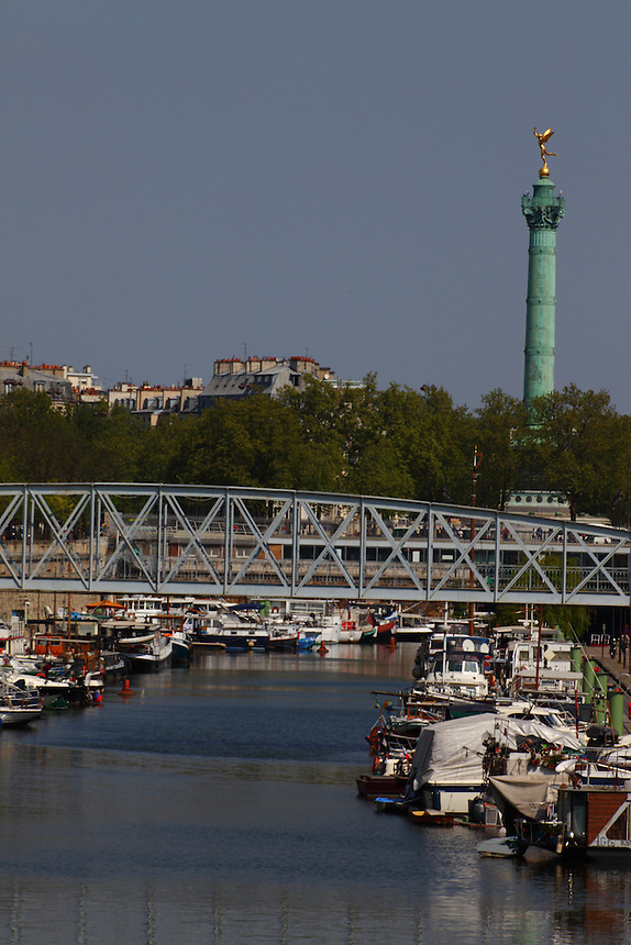 A view of the port de l'Arsenal in Paris (it links the Canal de Saint Martin to place de la Bastille), with its boats, its typical bridge, and the column of July on the background. Digitally Improved Photo.