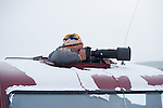 Photographer Grant Nakamura shooting wildlife from sunroof of a snowcoach in Yellowstone NP.