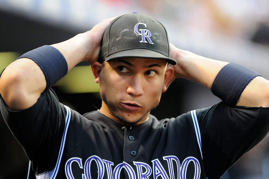 20 JULY 2011:    Colorado Rockies left fielder Carlos Gonzalez (5) pulls his hat on before heading out to the outfield  during a regular season game between the Atlanta Braves and the Colorado Rockies at Coors Field in Denver, Colorado. Rockies walked off against the Braves, winning 3-2 in 9 innings. *****For Editorial Use Only*****