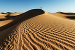 Traditional dressed Moroccan man with turban walks up a sand dune in the Sahara desert.