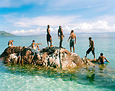 MADAGASCAR, group of men swimming and relaxing, Jardin Vanille Beach, Nosy Be