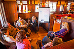 Mohonk Murder Mystery Weekend team meeting of Sam's Piano Players, with actress Alley Mulrain, to left of easel board, in Lake Lounge of Mohonk Mountain House, on March 10, 2012, in New Paltz, New York, USA.