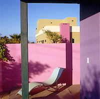 A sun-lounger is placed in a secluded corner of the terrace
