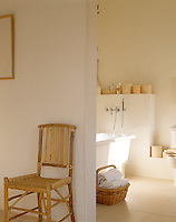 A wicker chair stands outside a calm and simple bathroom