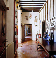 View down the hall which has a terracotta tiled floor