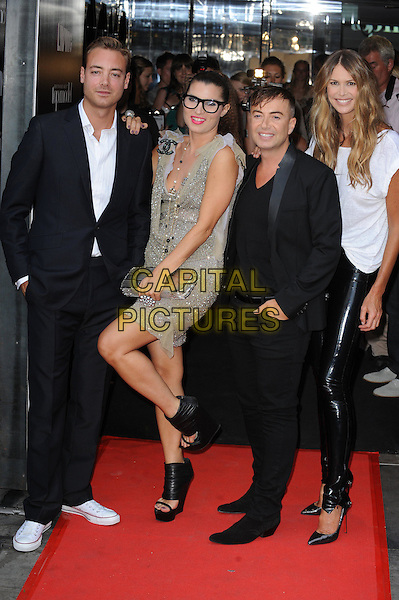 CHARLEY SPEED, GRACE WOODWARD, JULIEN MACDONALD & ELLE MACPHERSON .At the launch party for Series 6 of 'Britain's Next Top Model' held at Circus, Covent Garden, London, England, UK..June 30th 2010.full length shiny leggings black pvc rubber white top t-shirt bracelets pointy heels shoes Christian Louboutin glasses Chanel sparkly dress silver beaded green gold necklace brooch ring geek sequined sequin chiffon tulle platform wedges open toe leg up suit clutch bag.CAP/WIZ.© Wizard/Capital Pictures.