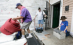 "Walter Blakesley (L) loads up the truck while his father, Buddy (L), holds onto his oxygen tank and son Andrew, 11 years-old, takes care of the family cat ""Alley"" as their family finishes packing up their belonging on Iberville St In New Orleans to evacuate to ""points north"" ahead of Hurricane Gustav August 31, 2008.    (Mark Wallheiser/TallahasseeStock.com)"