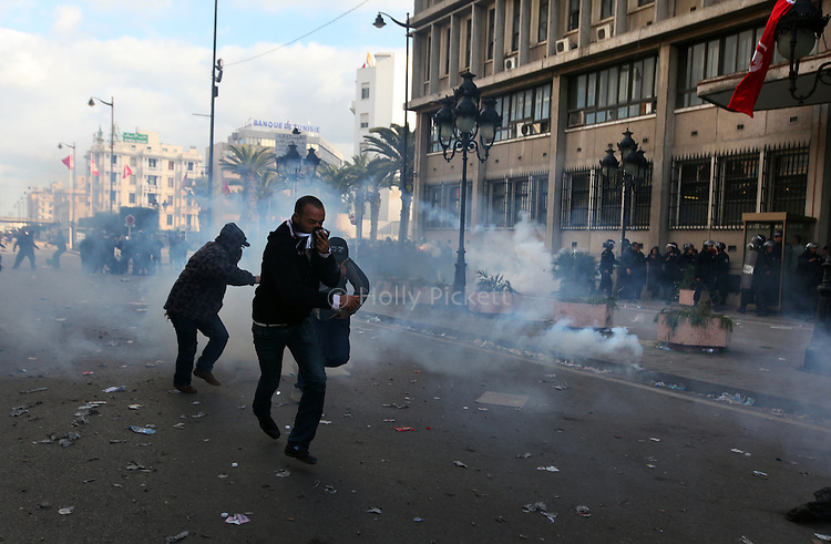 Demontrators run from tear gas outside the Interior Ministry in downtown Tunis, Tunisia, Jan. 14, 2011. Several thousand people gathered outside the Ministry to protest and ask President Zine El Abidine Ben Ali to resign.
