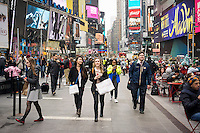 Tourists with their purchases in Times Square in New York on Friday, April 10, 2015. A strong dollar is making it less attractive to visit New York (and spend money!) possibly cutting into the tourism business. The tourism industry generates $60 billion dollars going into the New York economy. 55 million people visited the city last year with tourism jobs jumping 22% in the last decade.  (© Richard B. Levine)