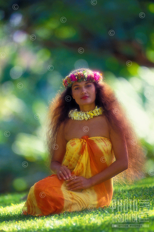 Beautiful Polynesian woman with traditional waist-length hair sitting on grass wearing an orange and yellow pareo, plumeria lei and traditional haku-lei floral headband.