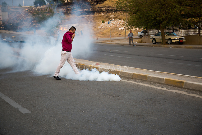 8/10/2015--Sulaimaniyah,Iraq--A photo of a protestor who is trying to take the tear gas away from other protestants.