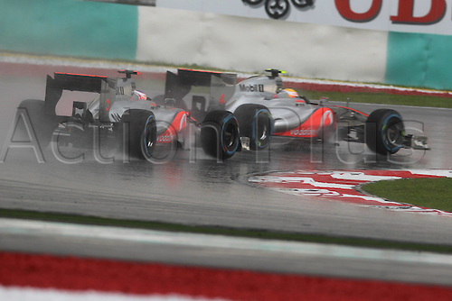 25.03.2012. Kuala Lumpur Malaysia.   FIA Formula One World Championship 2012 Grand Prix of Malaysia 3 Jenson Button GBR Vodafone McLaren Mercedes and 4 Lewis Hamilton GBR Vodafone McLaren Mercedes take a corner in heavy rain