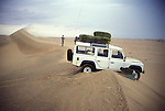 Land Rover stuck on top of  a sand dune,  Namib Naukluft desert.  Access is restricted due to Diamond mining activity by DeBeers.