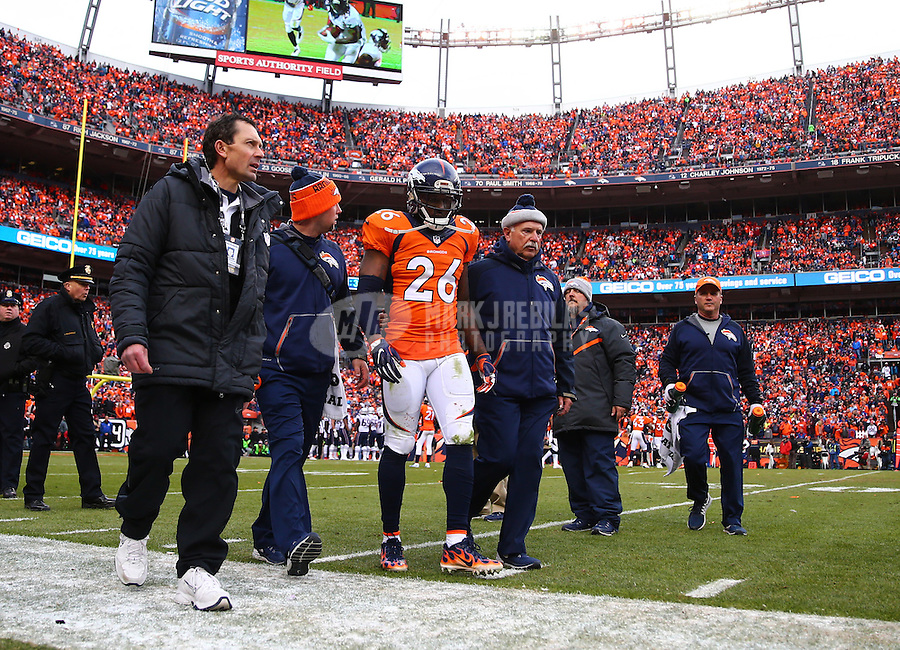 Jan 24, 2016; Denver, CO, USA; Denver Broncos defensive back Darian Stewart (26) is led off the field by trainers after suffering an injury against the New England Patriots in the AFC Championship football game at Sports Authority Field at Mile High. The Broncos defeated the Patriots 20-18 to advance to the Super Bowl. Mandatory Credit: Mark J. Rebilas-USA TODAY Sports