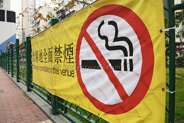 "Hong Kong, China, Asia. Hong Kong Kowloon. Large yellow bilingual banner in english and chinese at the entrance to a small urban park advising that ""Smoking is prohibited in this venue""."