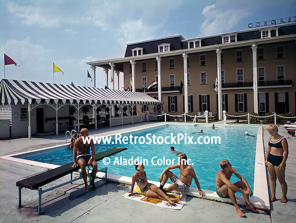 Couples sitting poolside in their bathing suits at the Congress Hall Hotel in Cape May, New Jersey. 1960's.