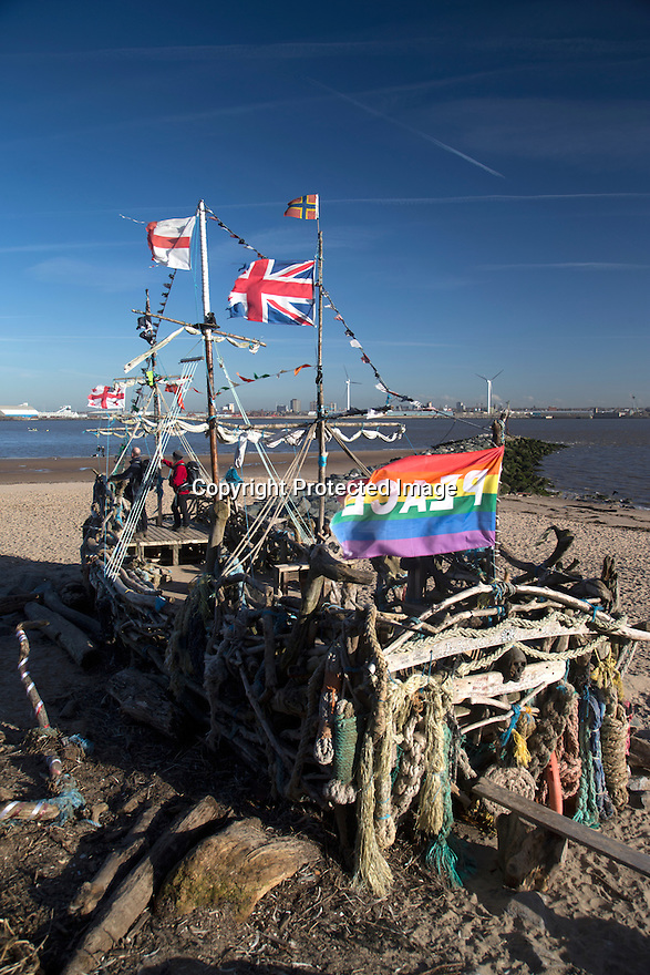 28/11/16<br /> <br /> As the cold front sweeps in with blue skies and freezing temperatures,  the Black Pearl pirate ship, made completely out of driftwood is photographed on New Brighton beach with the Liverpool skyline and Royal Liver Bird building in the background. The boat was built in 2013 by local artist Frank Lund and his friend Major Mace using materials found on their beach walks. The work of art has survived numerous storms and being set alight by vandals and is now a popular spot for tourists and locals alike. There was even a pirate wedding held on its deck last year.<br /> <br /> All Rights Reserved F Stop Press Ltd. (0)1773 550665   www.fstoppress.com