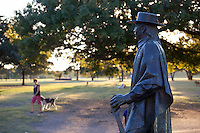 Stevie Ray Vaughan Statue overlooks Auditorium Shores as dogs play at the park in the background, Austin, Texas.