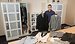Leo Torres, customer service coordinator in the Career Center on the Lincoln Park Campus, displays clothing items in the newly furnished Career Closet in SAC Room 151. Career Center staff noticed a need among students for professional clothes to wear to job interviews and founded the Career Closet. (DePaul University/Jeff Carrion)