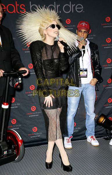 LADY GAGA (Stefani Joanne Angelina Germanotta) .attends the 2010 International Consumer Electronics Show (CES), the world's largest annual consumer technology trade show held at The Las Vegas Convention Center, Las Vegas, Nevada, USA, .7th January 2010..full length wig hair sunglasses round black sheer see through thru shoulder pads knitted knit ruched top  dress platform shoes heels microphone speaking hat hairspray.CAP/ADM/MJT.© MJT/AdMedia/Capital Pictures.