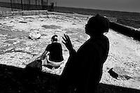 A Christian follower prays during a baptism ritual on the beach near the village of Cojímar, east of Havana, Cuba, 12 February 2009.