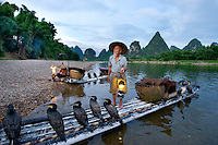 Li River, Yangshuo, China, 2010. Fisherman at dawn with cormorants,